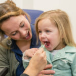 Kind waarbij wangslijmvlies wordt afgenomen met een wattenstaafje.