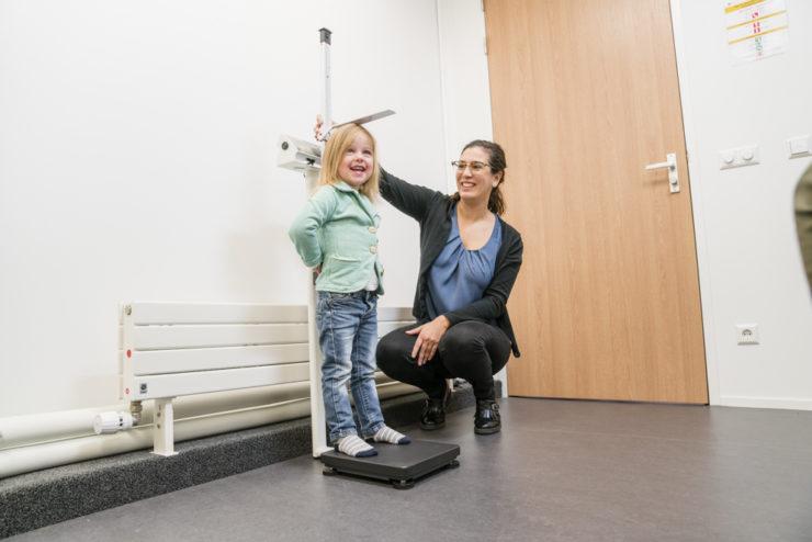 Een onderzoeksassistent meet de lengte van een meisje op